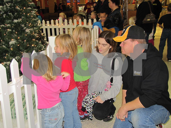 Jasmine, Courtney, and Crystal Hamilton, Sandra Hamilton, and Tim Hardman watch as the little girls wait to visit Santa at the Mall.