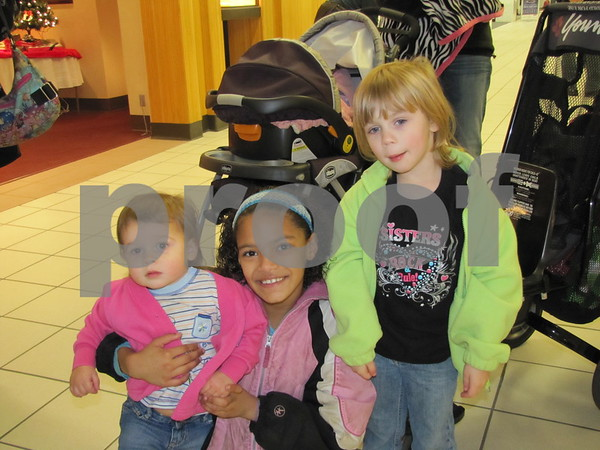 JC Brown (center) with Bailey and Serenity Feldman wait in line to visit Santa at the Crossroads Mall Saturday.
