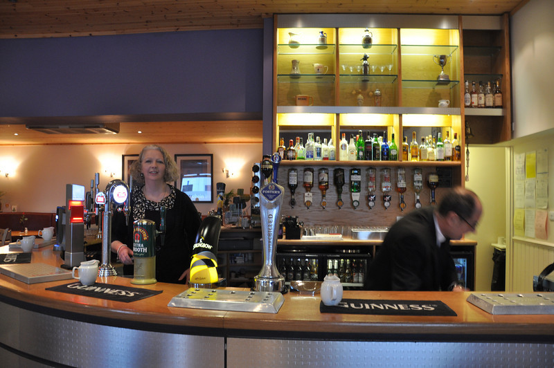 Husband and wife owners of the Chlachain Inn, Mallaig behind the bar getting ready for a busy day ahead.