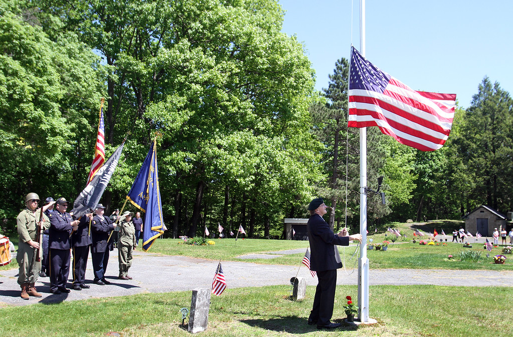 . Sgt. Carl McKoon of Shirley lowers and raises the flag during Memorial Day observance at Village Cemetery in Shirley. (SUN/Julia Malakie)