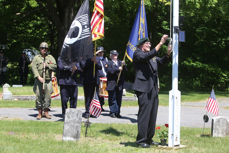 Sgt. Carl McKoon of Shirley lowers and raises the flag during Memorial Day observance at Village Cemetery in Shirley. (SUN/Julia Malakie)