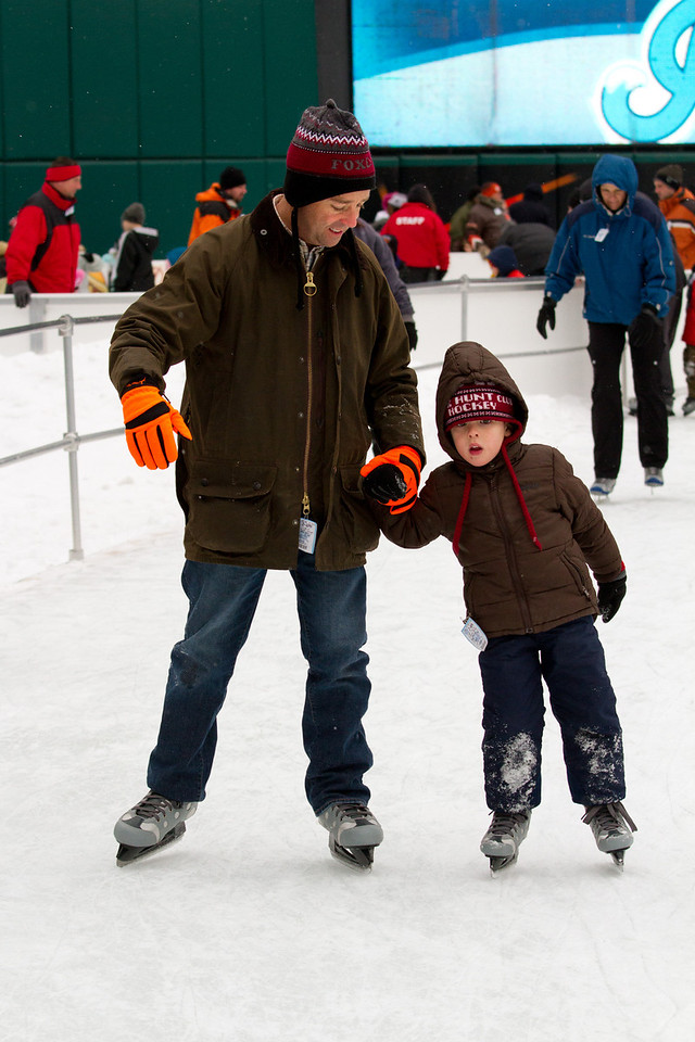 A father teaching his son how to ice skate.
