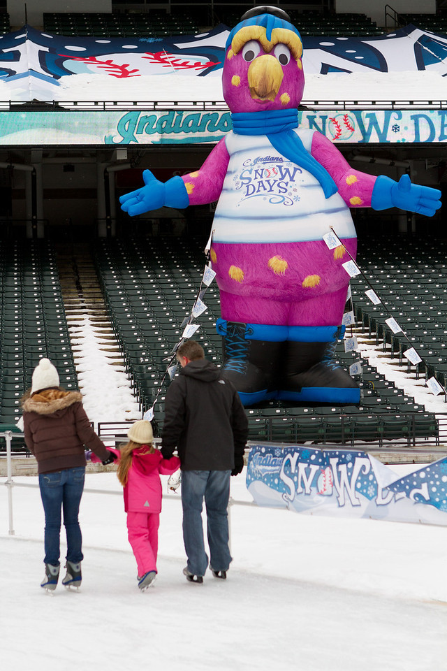 Slider greeting a family enjoying a nice stroll around the ice skating rink.