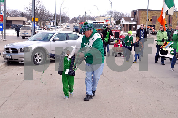 -Messenger photo by Joe Sutter<br /> <br /> Maddie Fisher and her great-grandpa Dennis Armstrong hand out green beads in the St. Paddy's Day parade. Armstrong was the parade Grand Marshall in 1992.