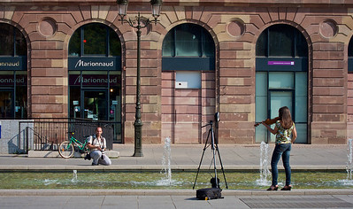 Man photographing woman playing violin at Place Kléber