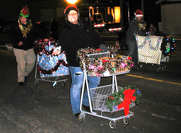Diane Raver | The Herald-Tribune<br /> Persons pushing decorated shopping carts make their way down the street.
