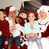 Debbie Blank | The Herald-Tribune<br /> Santa looks amazed at what Jacob Brock, 1, is telling him while brother Brian (left), 6; sister Emma, 3, and Mrs. Claus pose for photos. They are the children of Corey and Erica Brock, St. Leon. Their late great-grandfather John Campbell was a longtime Sunman Town Council member.