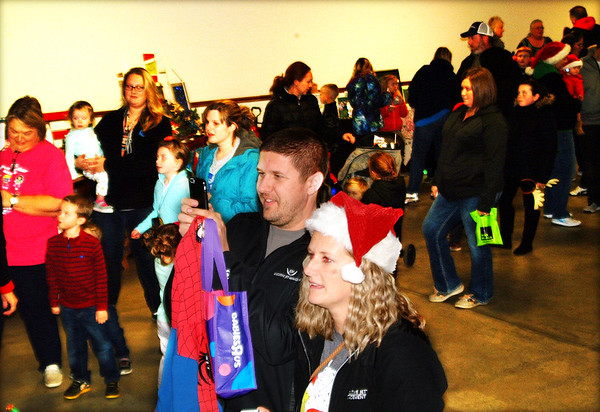Debbie Blank | The Herald-Tribune<br /> Kids daydream about their wish lists as they inch closer to Santa and Mrs. Claus, who greeted guests on the American Legion hall stage.