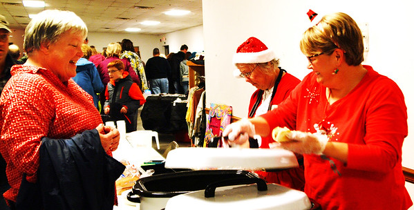 Debbie Blank | The Herald-Tribune<br /> Event co-organizer Carla Hacker (from right) and volunteer Pat Hollingsworth serve Pauline Chambers, Batesville, a hot dog in the American Legion hall.