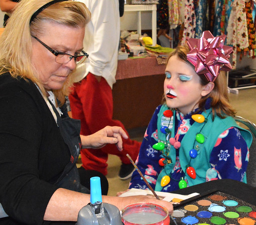 Debbie Blank | The Herald-Tribune<br /> Annie Back (left) gives Kayden Millson, 11, Sunman, a whole new look with face paints.