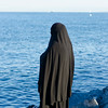 Lady in Burkha standing in front of the sea.