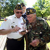 Tewksbury Memorial Day ceremony at Tewksbury Cemetery. Air Force veteran and guest speaker Joe Zangri, left, and Ed Flanagan, right, commander of Tewksbury American Legion, look at photos after the ceremony. At rear is John Hourihan. All are from Tewksbury. (SUN/Julia Malakie)