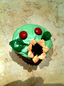 "The ""Paul is dead"" cupcake. This one COULD be just a innocent little sunflower with 2 ladybugs, if you didn't see that gas-mask signifying the End of Life As We Know It. Strawberry Fields Forever!"