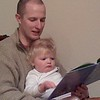 Tom reading the cow book to Aliceanna.