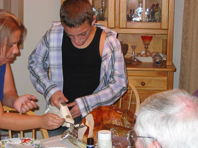 Rachel helps Paulie with the turkey carving.