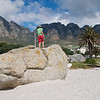 A chld plays on one of the large rocks at the north end of Camps Bay Beach