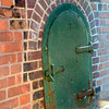 An old heavy metal door, with the wonderful old brick work to accent it all.