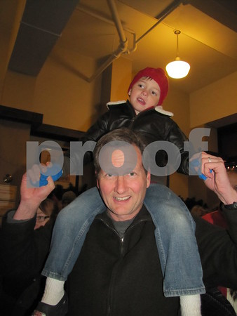 Chris Knobbe holds Thomas up over the crowd in line to visit Santa.