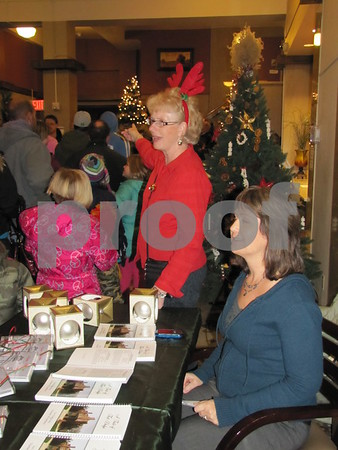Cindy Mulroney points the way toward Santa as Nancy Nevins is on hand selling Fort Dodge Christmas bulbs, cards, and cookbooks.  The items can also be purchased at the Chamber and some businesses downtown.