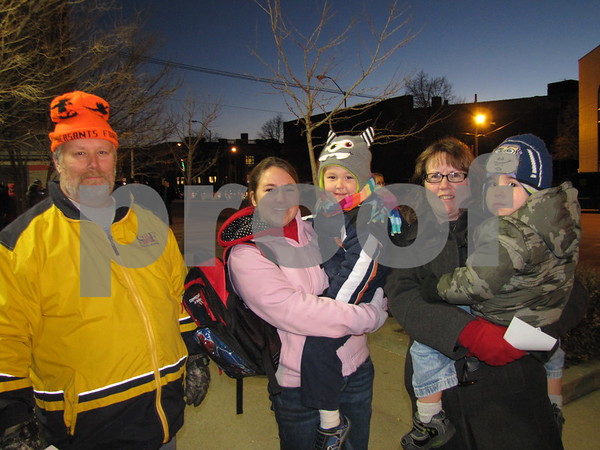 Greg Lombard, Sara Sankey holding Mason, and Karen Lombard holding Gavin, braved the cold to welcome Santa to Fort Dodge at the Tree Lighting Ceremony downtown.