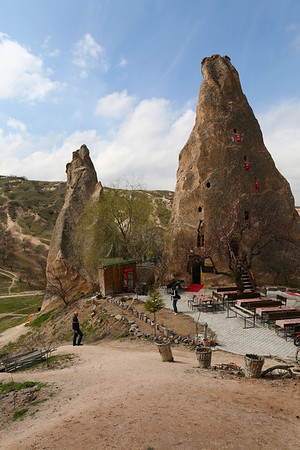 Uçhisar is a nearby village with a natural rock citadel. You can either drive to the top or walk for a while. Some of the houses on the way up have been converted to restaurants like the one in picture.