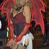 A young man dressed as a devil girl wearing a corset, fishnet stockings and devil wings is holding a naughty secret in his hands