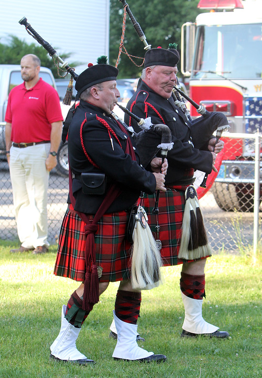 . Flag retirement ceremony for Flag Day at Nabnasset American Legion Post 437 in Westford. Winchester F.D. Capt. Rick Tustin, left, and Westford F.D. Lt. Donald Parsons, right, members of the Westford District Pipes & Drums, play bagpipes.  (SUN/Julia Malakie)