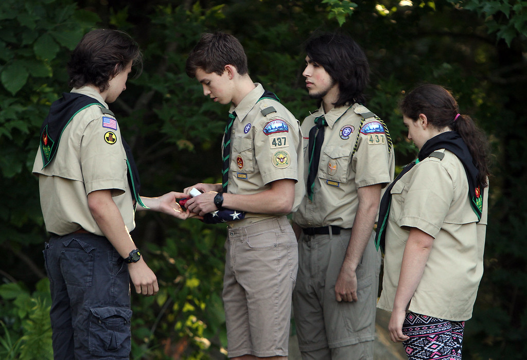 . Flag retirement ceremony for Flag Day at Nabnasset American Legion Post 437 in Westford.  Members of Boy Scout Troop 437, from left, Ian Anderson, Ben McQuinn, Max Mazgalis, and Mairead Catalano-Foley, fold up the just lowered old flag. (SUN/Julia Malakie)