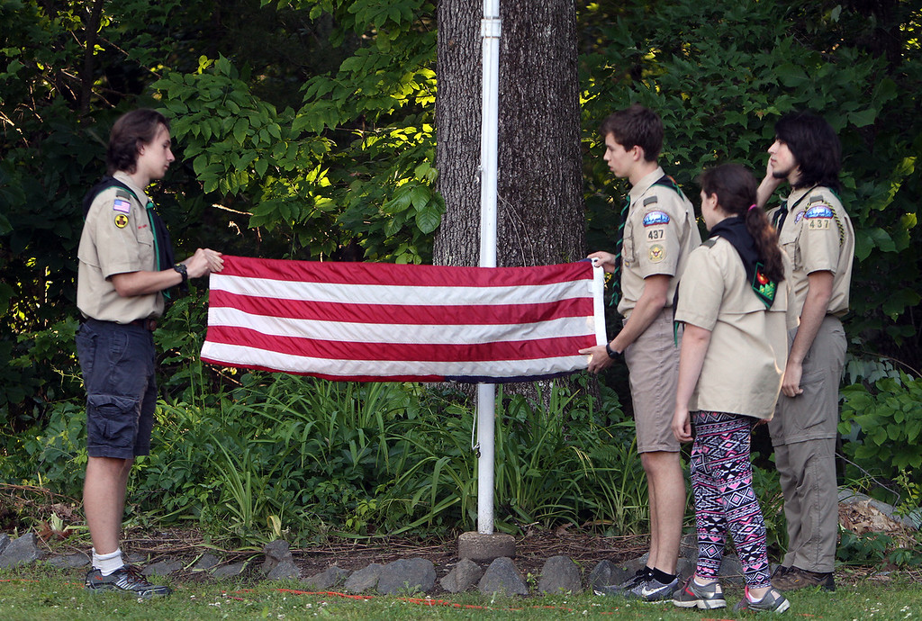 . Flag retirement ceremony for Flag Day at Nabnasset American Legion Post 437 in Westford.  Members of Boy Scout Troop 437, from left, Ian Anderson, Ben McQuinn, Mairead Catalano-Foley, and Max Mazgalis, fold up the just lowered old flag. (SUN/Julia Malakie)