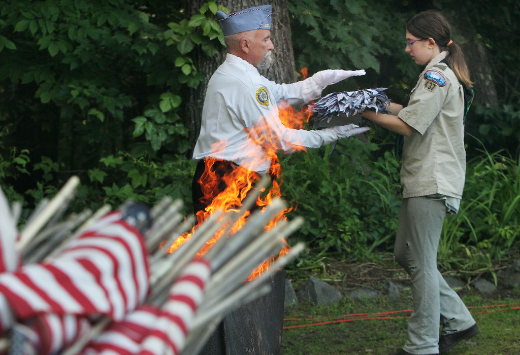 . Flag retirement ceremony for Flag Day at Nabnasset American Legion Post 437 in Westford. Lauren Mazgelis, 13, of Westford and Boy Scout Troop 437 hands over for retirement the stars from a very large flag that had to be disassembled for the ceremony, to David DePaulis, headmaster of arms for Sons of American Legion.  (SUN/Julia Malakie)