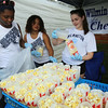 Groups prepare their booths for 4th of July activities on Wilmington Town Common. From left, Wilmington High cheerleaders Britney Mallebranche, 17, Mekhi-la DeRosa, 17, and Abby Callahan, 15, fill popcorn bags at their team's booth. (SUN/Julia Malakie)