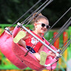 Emelia Malm, 5, of Burlington, rides the chair swing at 4th of July activities on Wilmington Town Common. (SUN/Julia Malakie)