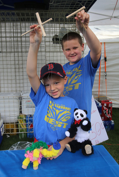 Groups prepare their booths for 4th of July activities on Wilmington Town Common. Logan C., 7, and Spencer Talbot, 9, rear, unpack marionettes at the Cub Scout Pack 56 booth. (SUN/Julia Malakie)
