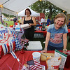 Groups prepare their booths for 4th of July activities on Wilmington Town Common. Michelle Fregeau, left, and Sarah Cosman, both of Wilmington, set up the St. Elizabeth's Episcopal Church booth. (SUN/Julia Malakie)