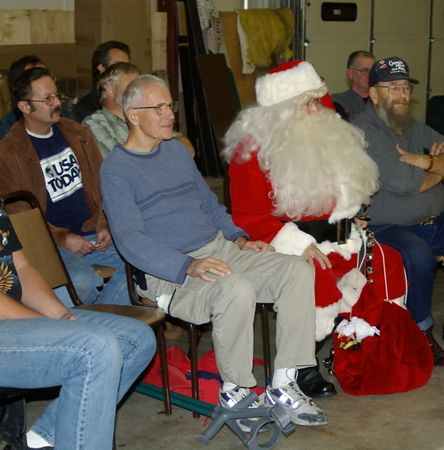 "<font size=""3"">Santa relaxes during a presentation </font><br>Return to <a href=""http://www.omahawoodworkers.com/"">Woodworkers Guild</a><br>"