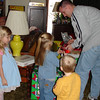 Daddy handing out gifts to the deliverers 2 12-17-05