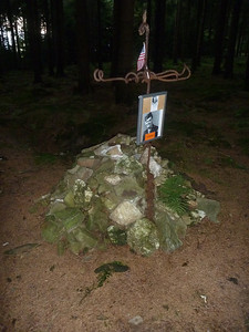 Laid all around and on this memorial to fallen soldiers are bullets and shell fragments found in the forest