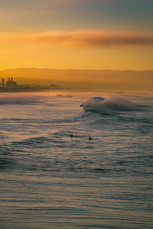 The curling lip of a large wave rolls past two sunrise surfers in Manhattan Beach, CA.