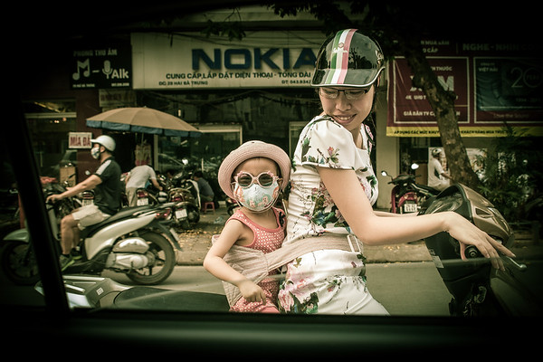 Young girl on the back of a scooter in Hanoi, Vietnam