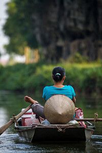 In Tam Coc (the three caves) a beautiful winding river runs through caves. Women who row their boats wit their feet cruise the river and sell food and drinks.