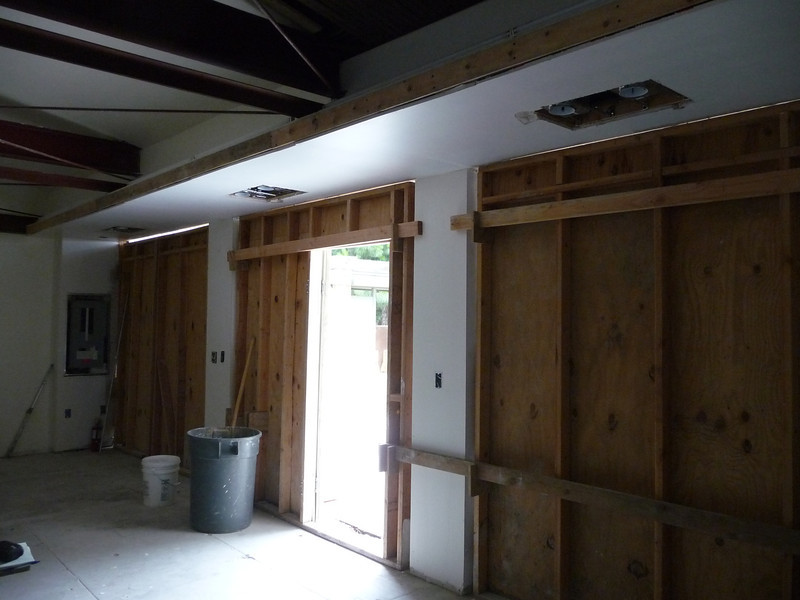 "Interior of the garage, south wall.  All of the steel columns and perimeter I-beams have been furred out and covered, and the walls and ceiling have been primered.  Three sets of large ""barn doors"" will be reproduced based on early photographs."