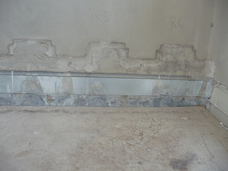 Art stones have been removed from the roof parapet over the south hallway, adjacent to the living room entry.  You can see that the galvanized sheet metal flashing is corroded - a sure sign that water had gotten trapped behind the art stones.