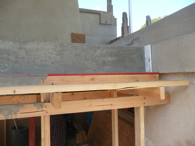 """Notice at the end there is a sheet of 1/2"""" thick styrofoam.  This beam will no longer be connected to the house from the ends, only from behind and below.  This is in case of an earthquake, the beam will have room to move without pounding the sides of the house."""