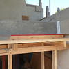 "Notice at the end there is a sheet of 1/2"" thick styrofoam.  This beam will no longer be connected to the house from the ends, only from behind and below.  This is in case of an earthquake, the beam will have room to move without pounding the sides of the house."