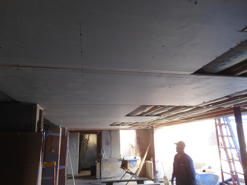 The living room entry and the south hallway ceilings are being covered with gypsum panels.  At a later date, these panels will be covered with a finish coat of plaster.  This is one of the few areas where we are using gypsum since there is nothing left of the original ceiling or floor.