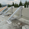 Aluminum A-frame brackets are being installed on the backside of the roof parapet over the living room.