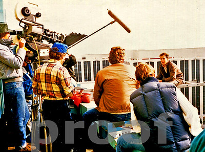 Bruce Willis (sitting on the right side of frame) on location for the pilot of the hit tv series MOONLIGHTING.  Chuck Cohen camera operates his Panavision Camera on left, filmed in Los Angeles in August, 1984