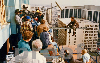 Bruce Willis sits on ladder on location in downtown Los Angeles during filming of the MOONLIGHTING TV Series Pilot.  Chuck Cohen camera operates on left side of image.  August, 1984.