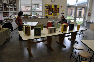 Art teacher, Barbara Mandell and poet, Frank Soos, chat admist middle school boxes.