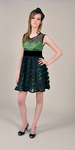 Green cocktail dress with black polka dot foe neckline and overskirt; exposed zipper and button fastening